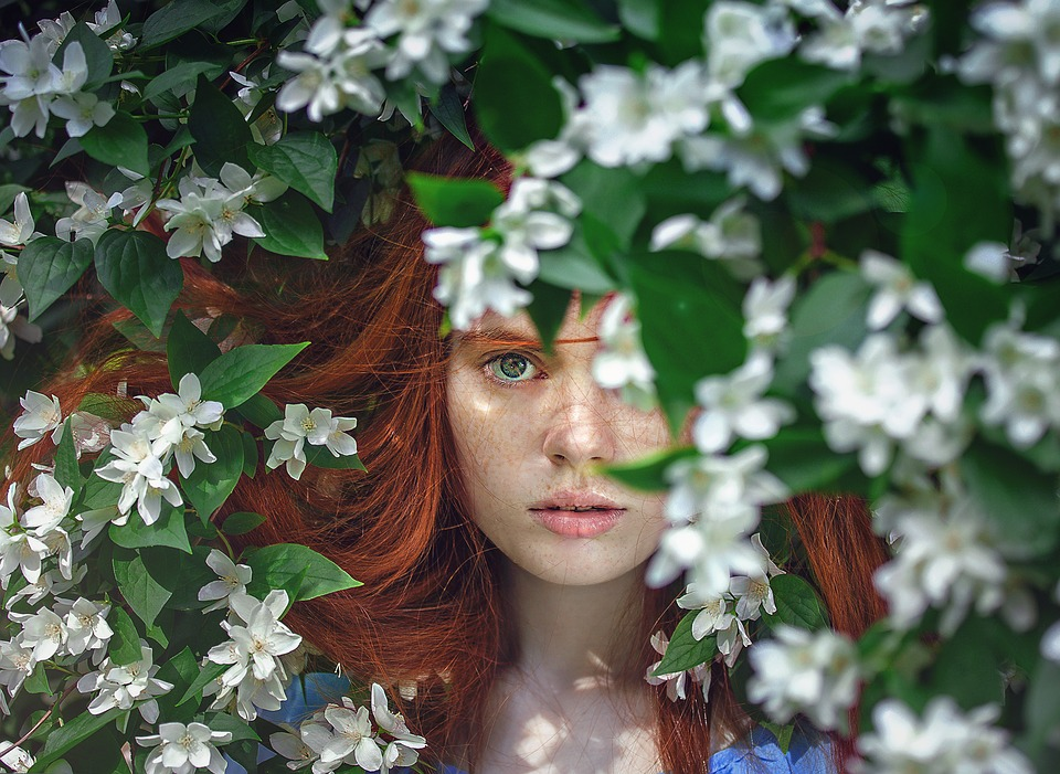 woman with beautiful skin behind spring branches